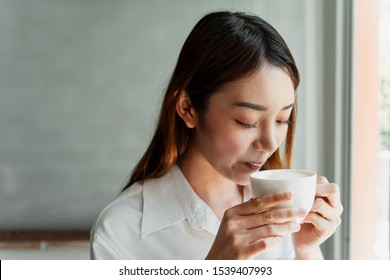 Office girl taking a sip from a cup of coffee, leaving milk foam at her lips.