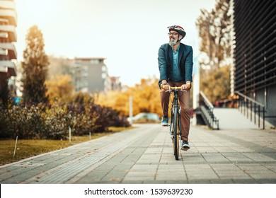 Un apuesto hombre de negocios casual de mediana edad va a la oficina en bicicleta. Conduce una bicicleta frente al distrito de oficinas.