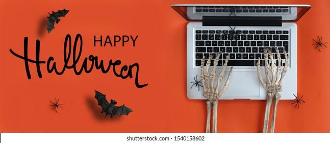 Manos de esqueleto escribiendo en una computadora portátil y texto de Feliz Halloween