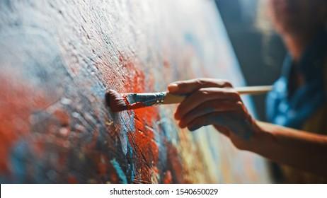 Künstlerin arbeitet an abstrakten Ölgemälden, bewegt Pinsel energisch Sie schafft moderne Meisterwerke. Dunkles Kreativstudio, in dem große Leinwand auf Staffelei beleuchtet steht. Nahwinkel-Nahaufnahme