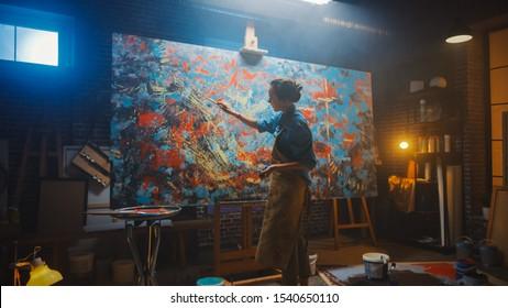 Talentierte Künstlerin, die an einem modernen abstrakten Ölgemälde arbeitet und mit breiten Strichen unter Verwendung des Pinsels gestikuliert. Dark Creative Studio Großes Bild steht auf Staffelei beleuchtet, Werkzeuge überall