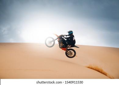 Piloto en una motocicleta de cross-country saltar en el desierto