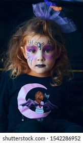 A Portrait of a little child girl with a halloween makeup on the dark background.