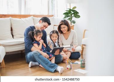 タブレット、ラップトップを使用してゲーム鑑賞映画を再生し、ライフスタイルの概念のために家でリラックスして幸せなアジアの家族