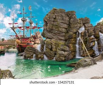 Piratenschiff im Rückstau der tropischen Pirateninsel, mit großem Felsen in Form eines Schädels in der Nähe