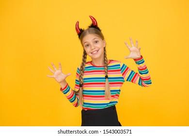 Zij duivel. Halloween-partijmeisje gele achtergrond. Het meisje draagt een hoofdband van rode duivelshoorns. Mysterieus meisje met Halloween-look. Klein meisje veranderde in een boze demon.