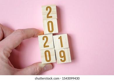 Hand verschiebt Holzwürfel mit den Nummern 2019 bis 2020 auf rosa Hintergrund. Konzept der Veränderung im kommenden neuen Jahr.