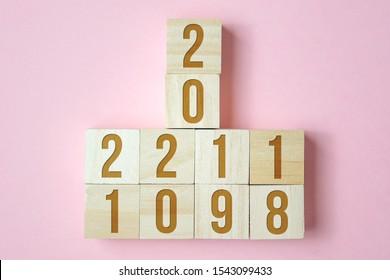Verschiebung von Holzwürfeln mit Zahlen von 2018 bis 2021 auf rosa Hintergrund. Konzept des neuen Jahres.