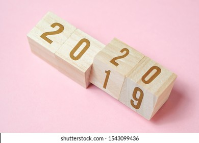 Zahlen 2019 ändern sich zu 2020 auf Holzwürfeln auf rosa Hintergrund. Konzept des neuen Jahres.