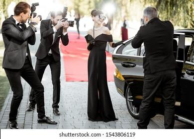 زن زیبایی که به عنوان یک بازیگر مشهور سینما در حال ورود به مراسم اهدای جوایز به سبک یکپارچهسازی با لباس است و خبرنگاران عکس از او عکس می گیرند