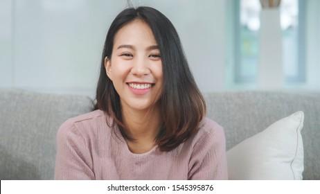 自宅のリビングルームでリラックスしながら、笑顔でカメラを見て幸せな10代のアジアの女性。