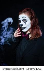 Make-up für Halloween: Bild einer Frau in einem Joker-Make-up, das raucht