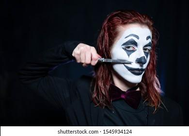 Make-up für Halloween: Bild einer Frau in einem Joker-Make-up mit Messer