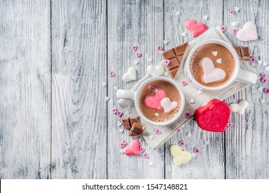 Valentines day treat ideas, two cups hot chocolate drink with marshmallow hearts red pink white color with chocolate pieces, sugar sprinkles, old wooden background copy space top view