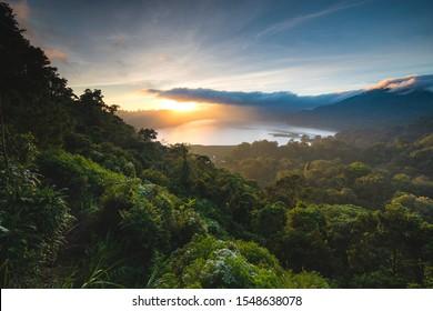 Schöner Sonnenuntergang über See Buyan Bali Indonesien. Inselküstenlandschaft Naturlandschaft. Erstaunliche Aussicht auf grüne Büsche und Bäume Forest Jungle Hill, bewölkter Himmel und Sonne. Küste vom Aufstieg