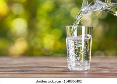 Verter el agua de la jarra en un vaso sobre una mesa de madera al aire libre