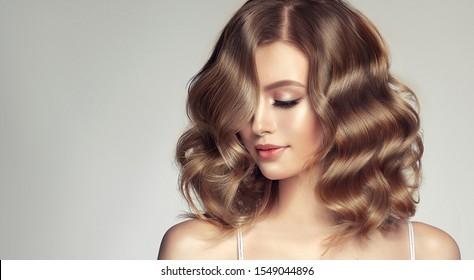 灰色の背景に巻き毛の美しい髪の女性。美しさのある女の子は心地よい笑顔。短いウェーブのかかった髪型