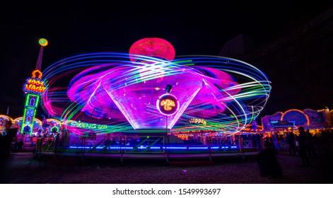 montaña rusa en la Herbstmesse (feria de otoño) en Basilea con coloridos senderos de luz mientras está en acción