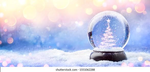 金色の光と雪の上のスノードームの光沢のあるクリスマスツリー