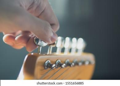 Stimmen der Gitarrensaite durch Einstellen der Stimmmaschinen