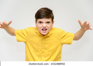Concept boy teenager shows imitates the behavior of heroes from different movies. Portrait of a child on a white background in a yellow shirt. Standing in front of the camera in poses with emotions.