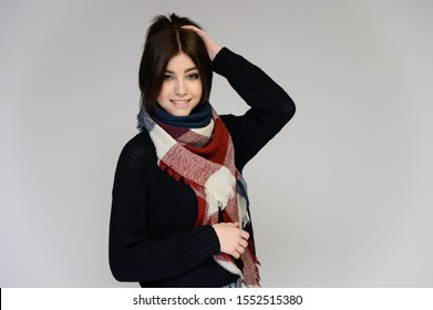 Close-up portrait of a young pretty girl student with long black hair with a scarf and in a sweater, on a white background. Standing right in front of the camera in different poses with emotions.