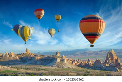 Surise view of unusual rocky landscape in Cappadocia, Turkey. Colorful hot air balloons fly in blue sky over amazing valleys with fairy chimneys in Cappadocia.