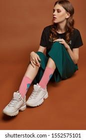 Voller Schuss eines jungen europäischen Mädchens in weiter grüner Hose, T-Shirt mit schwerem Metallbandnamen, weißen Turnschuhen und rosa Socken mit bedruckter blauer Muschel. Das Mädchen posiert auf dem braunen Hintergrund.