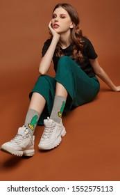 Vollaufnahme eines jungen europäischen Mädchens in weiten grünen Hosen, T-Shirt mit Heavy-Metal-Bandnamen, weißen Turnschuhen und grauen Socken mit bedrucktem Kaktus. Das Mädchen posiert auf dem braunen Hintergrund.