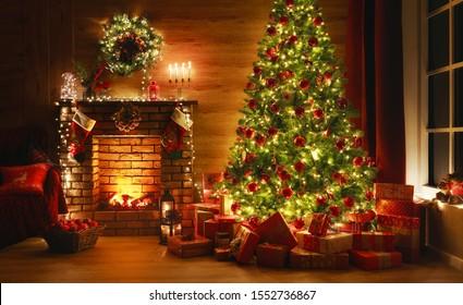 interieur kerst. magische gloeiende boom, open haard, geschenken in het donker 's nachts