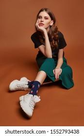 Vollaufnahme eines jungen Mädchens in weiten grünen Hosen, T-Shirt mit Heavy-Metal-Bandnamen, weißen Turnschuhen und blauen Socken mit figürlichem Rand und Erdbeerdruck. Das Mädchen posiert auf dem braunen Hintergrund.
