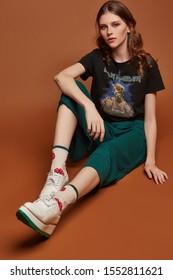 Voller Schuss eines jungen Mädchens in weiter grüner Hose, T-Shirt mit schwerem Metallbandnamen, weißen Schuhen und beigen Socken mit schwarzem Rand und Erdbeerdruck. Das Mädchen posiert auf dem braunen Hintergrund.