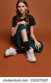 Vollaufnahme eines jungen europäischen Mädchens in weiten grünen Hosen, T-Shirt mit Heavy-Metal-Bandnamen, weißen Turnschuhen und schwarzen Socken. Das Mädchen posiert auf dem braunen Hintergrund.