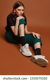"""Vollaufnahme eines Mädchens in weiten grünen Hosen, T-Shirt mit Heavy-Metal-Bandnamen, weißen Turnschuhen und schwarzen Socken mit weißer Schrift """"Dein Leben ist ein Witz"""". Das Mädchen posiert auf dem braunen Hintergrund."""