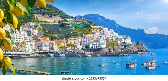 Panoramablick des schönen Amalfi auf Hügeln, die zur Küste, Kampanien, Italien führen. Die Amalfiküste ist das beliebteste Reise- und Urlaubsziel in Europa. Reife gelbe Zitronen im Vordergrund.