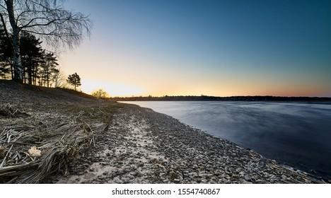 Sonnenuntergang an der Flussküste. Glattes Wasser am Fluss