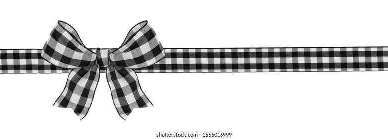 黒と白の水牛格子縞のクリスマスプレゼントの弓と白い背景で隔離のリボンの長い境界線