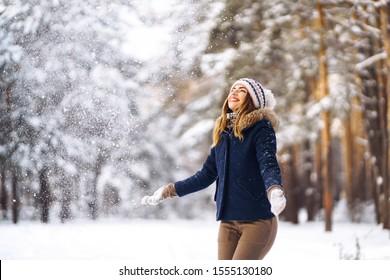 Glückliche junge Frau spielt mit einem Schnee im sonnigen Wintertag. Mädchen genießt Winter, frostigen Tag. In den Winterferien spielt eine Frau mit Schnee und wirft weißen, losen Schnee in die Luft. Spazieren Sie im Winterwald.