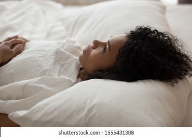 Exhausted African American woman with open eyes lying in bed under white blanket, tired girl with curly hair suffering from insomnia, lack of sleep, early morning awakening concept, close up