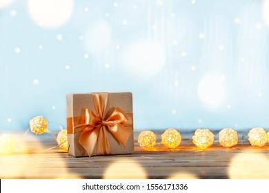 Caja de regalo o presente envuelta con papel artesanal y cinta con luces de guirnalda en mesa de madera. Fondo de vacaciones de feliz Navidad y año nuevo.