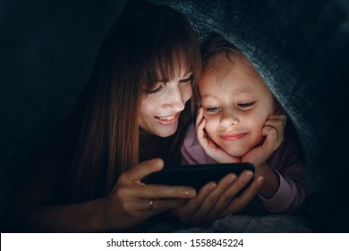 Mother with a little daughter watching content on  smartphone in the dark under the blanket covers.