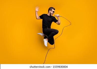 クレイジーヒップスターの男の全身プロフィール写真は、マイクを持って高くジャンプし、音楽愛好家が好きな歌を歌っています。太陽のスペックを着用してください。