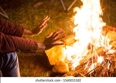 Mann, der seine kalte Hand über Campingfeuer auf einem Campingplatz in den Bergen aufwärmt.