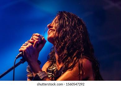 女性ミュージシャンがステージでのパフォーマンス中に観客と一緒に歌ったり笑ったりしながら、ローアングルから見ています