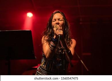 赤信号のステージでの演奏中に目を閉じて歌う女性ミュージシャンをローアングルから見た