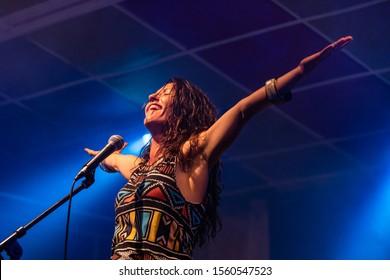 女性ミュージシャンは、パフォーマンス中に両手を上げて歌い、観客と笑顔で歌いながら、ローアングルから見ています。