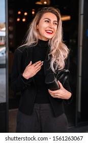 lächelndes blondes Mädchen in einem schwarzen Anzug auf einem schwarzen Hintergrund