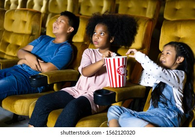 Kid group see movie in theater with friends. They eat a popcorn. Multiplex with yellow seat.