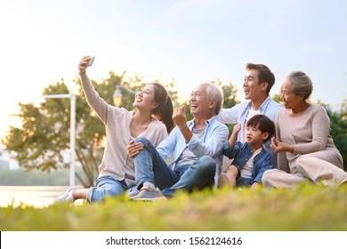 公園で屋外で携帯電話を使用してselfieを取る草の上に座っている3世代の幸せなアジアの家族