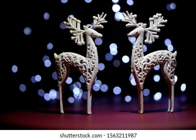 Christmas decoration with two white dears on background with lights.